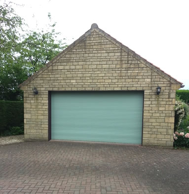 A roller garage door in chartwell green