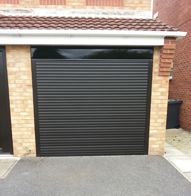 A black garage door on rollers