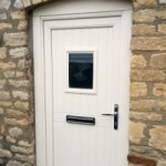 Secure composite front door by Apeer, installed by Cliffside Windows in Lincolnshire. Cream front door in a stone wall with glazed window.